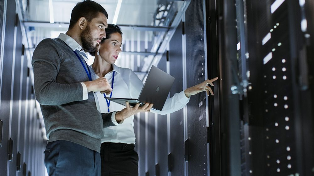 Picture of two persons working in a data center